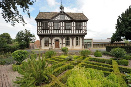 Image shows Grange Court, a beautiful building with a garden in front with shaped hedges.
