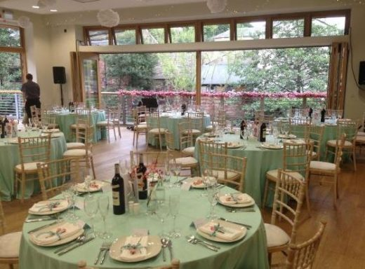 Image shows a room with folding doors that look out into trees at Hebden Bridge Town Hall. The room is dressed for a wedding.