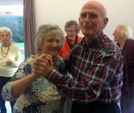 An older couple smiling at the camera while they dance
