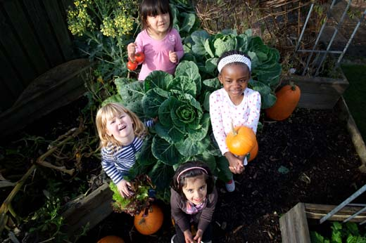 Four children looking up to the camera, they are standing around a huge cabbage in the permaculture garden