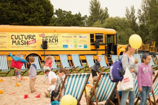 Image shows a yellow bus in the background with a giant sandbox with deck chairs and kids playing