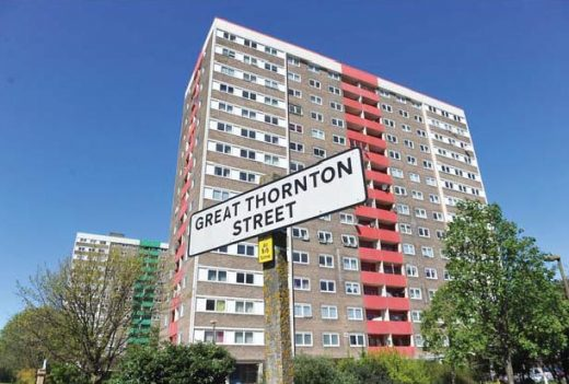 A large multistory block of flats, with a sign in front that reads Great Thornton Street