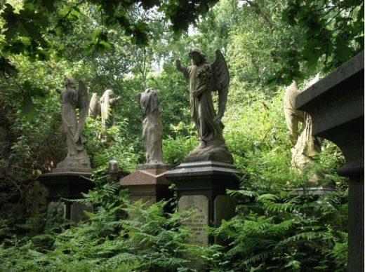 A wooded cemetary with three angel statues on top of the tombs.