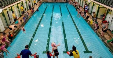 Bramley baths pool, lots of adults and children are around the edge jumping into the pool